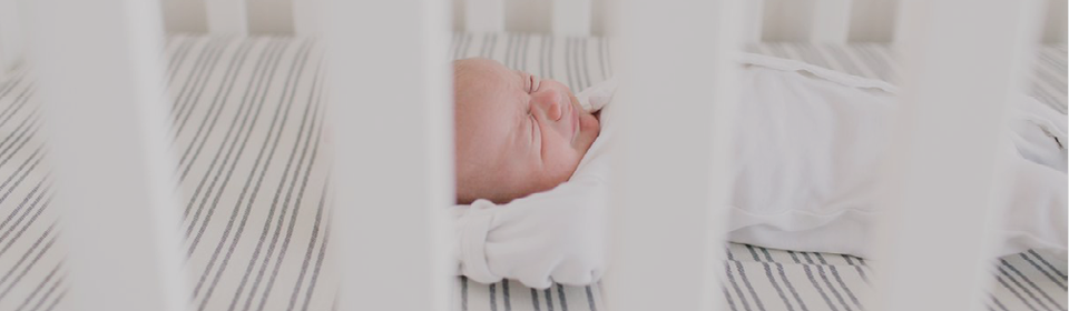 Baby sleeping in L'ovedbaby gown in crib with Copper Pearl crib sheets