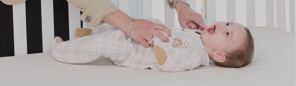 Mom tickling baby while they're laying on a Naturepedic crib mattress