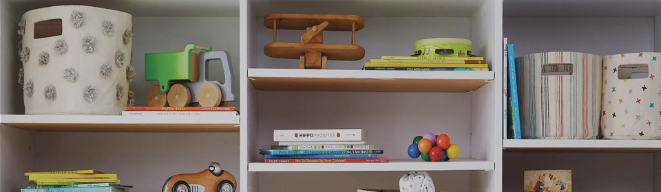 Shelving unit with toys, accessories and Petit Pehr storage bins