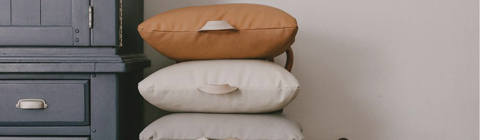Three Gather floor cushions stacked on a chair