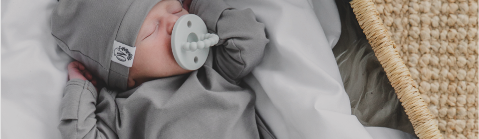Little baby with Ryan & Rose pacifier in mouth wearing grey Over Company nodo gown and hat