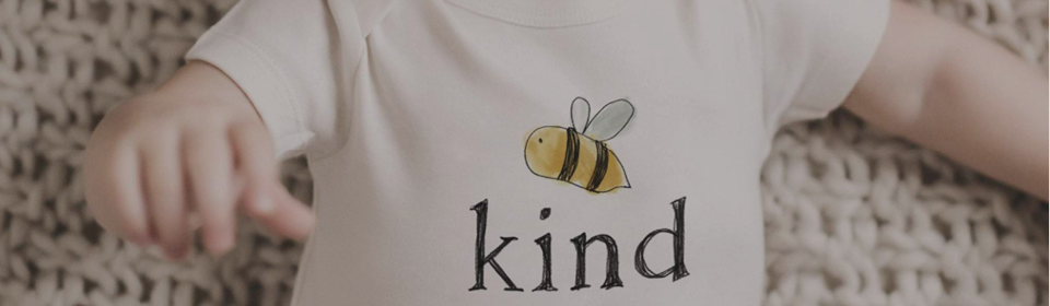 Baby wearing a Finn and Emma onesie that says Be Kind with a bumble bee