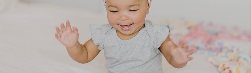 Little girl laughing with hands up in a LouLou Lollipop grey bodysuit