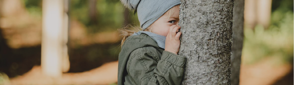 Little girl in Calikids hat and scarf hiding behind tree