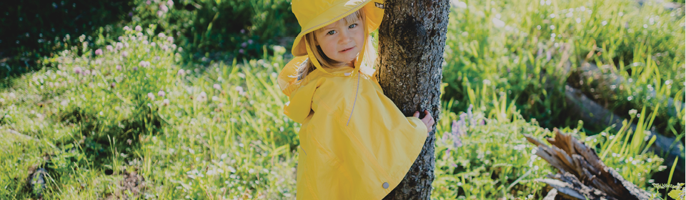 Little girl wearing yellow Calikids rain poncho and hat