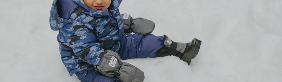 Little boy wearing matching grey Stonz Wear Inc gloves and winter boots sitting in the snow