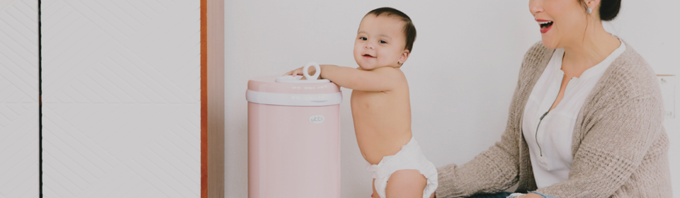 Baby hitting a pink Ubbi diaper pail while mom holds them up