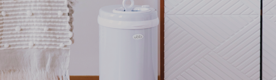 Ubbi diaper pail in white sitting in front of a nursery dresser with change table