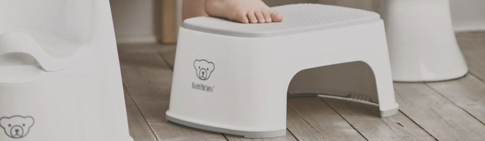 Little girl stepping up on a white non-slip step stool by Babybjorn