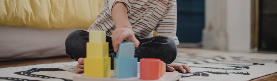 Little boy sitting on a playmate playing with Jan wooden blocks in yellow, blue and red