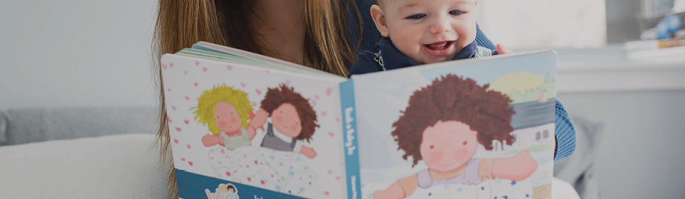 Mom reading a smiley baby a Lulujo book