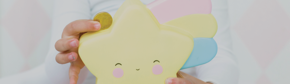 Little girl putting a coin in A Little Lovely Company shooting star piggy bank