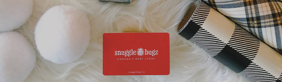 Snuggle Bugz Gift Card sitting on fur carpet with wrapped paper beside it
