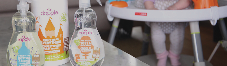 Dapple cleaning products on table with little girl in a Skip Hop activity centre in the background