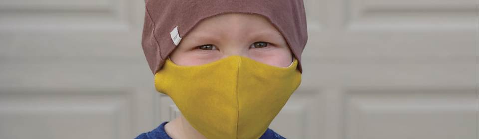 Little boy wearing a yellow face mask with a burgundy beanie