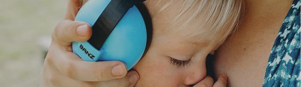 Mom holding little boy in arms wearing blue baby banz ear protection covers