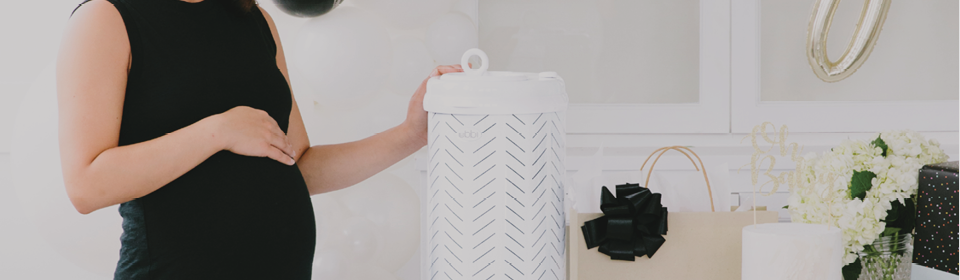 Pregnant mother at her Baby Shower opening gifts of a diaper pail with hand on stomach