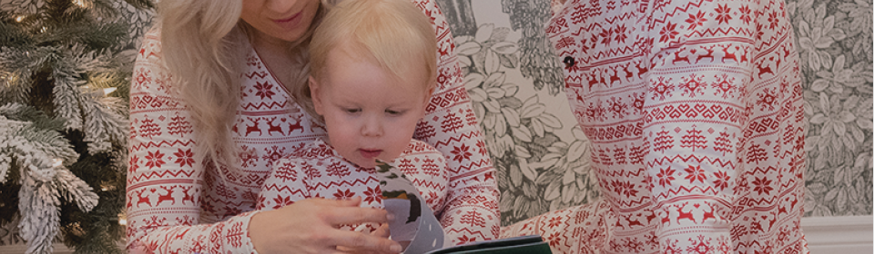 Parents in matching holiday pyjamas reading book to child