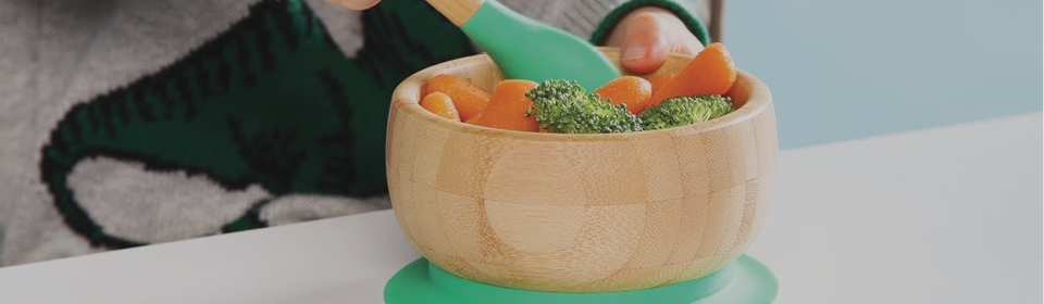 Baby using Avanchy spoon to eat vegetables out of matching silicone bamboo bowl