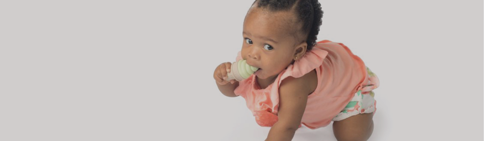 Baby girl crawling with a Baby SweeTooth ice cream teether in mouth