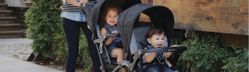 Mother pushing 2 children in black Baby Trend Sit N' Stand double stroller