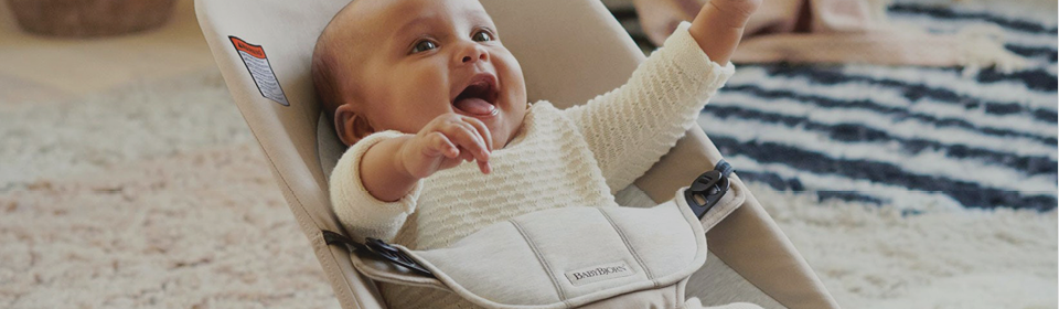 Smiling baby in a BabyBjörn bouncer bliss in cotton