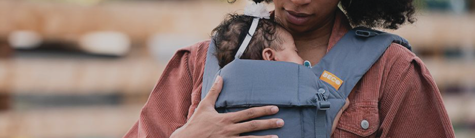 Mother using a grey BECO baby carrier to carry baby girl