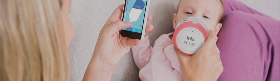 Mother feeding with Bluesmart MIA Smart Baby Bottle and tracking with app on iPhone