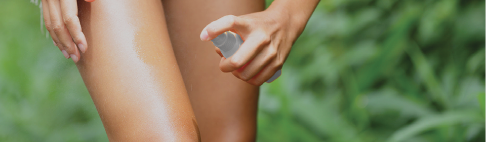 Women spraying Care Plus insect repellent on her leg while outside