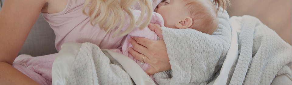 Mother breastfeeding baby using the Arm Here For You by Cheryl's Home & Family blanket