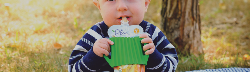 Little boy in park drinking puree with DahdoOo lil grip bottle and pouch holder