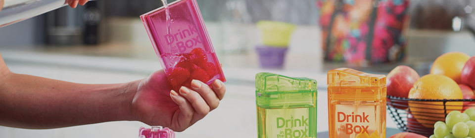 Drink In The Box containers sitting on kitchen counter while mom pours water in one with raspberries