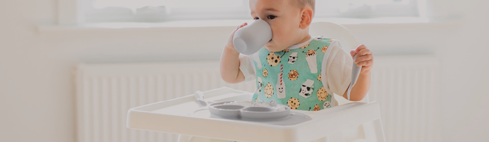 Baby in high chair drinking and eating from EZPZ silicone mealtime accessories in a BabyBapron bib