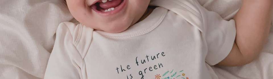 Baby smiling wearing Finn & Emma The Future is Green graphic organic bodysuit onesie