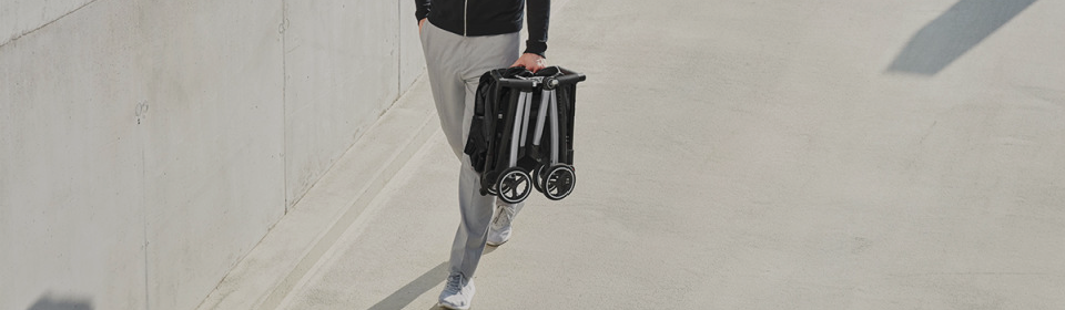 Man holding Goodbaby Pockit+ Compact Stroller