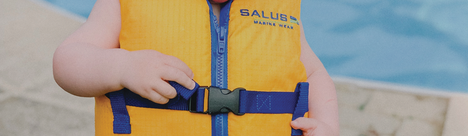 Little boy wearing Salus Marine Nimbus life jacket vest while standing in front of a swimming pool