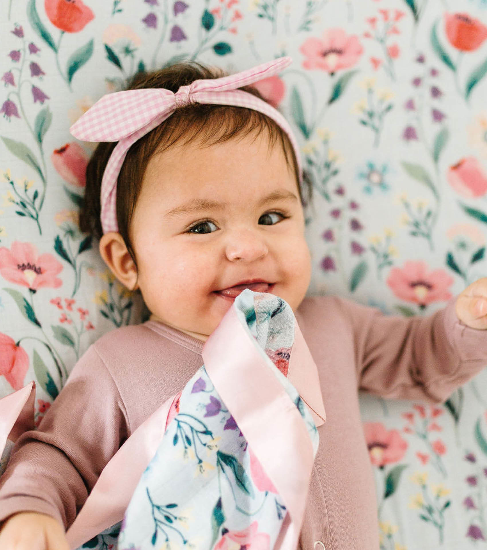 Baby with LouLou Lollipop swaddle and matching security blanket in floral print