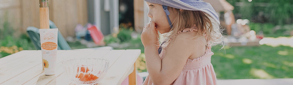 Little girl eating watermelon at a picnic table with Green Beaver sunscreen for kids beside her