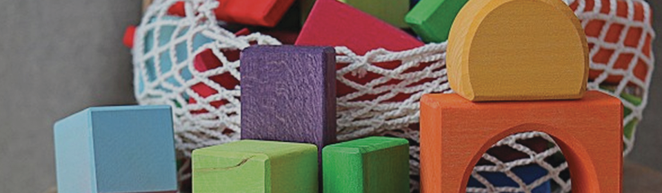 Grimm's rainbow coloured blocks stacked on floor
