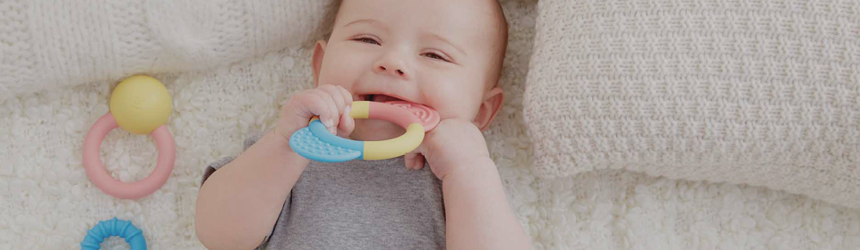 Baby chewing on Hape pastel rattle and teething rings