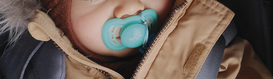 Baby with herobility blue pacifier in mouth