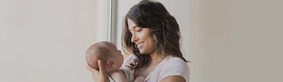 Mom holding baby after giving them Infacol colic relief drops