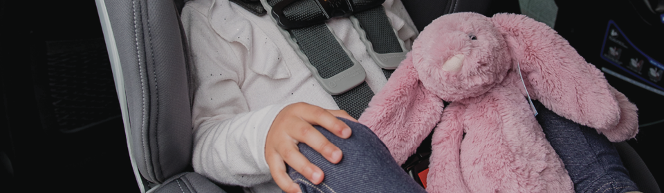 Little girl in Britax Boulevard ClickTight Convertible Car Seat holding pink Jellycat bunny