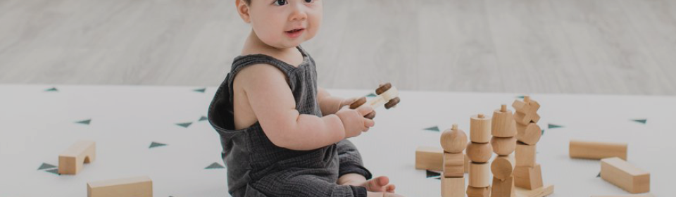 Little boy playing with wooden blocks on a Little Bot reversible activity mat