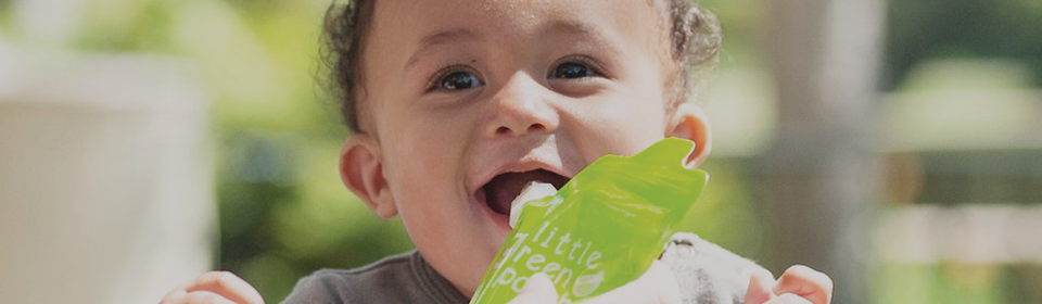 Mom feeding baby boy food in a reusable Little Green Pouch