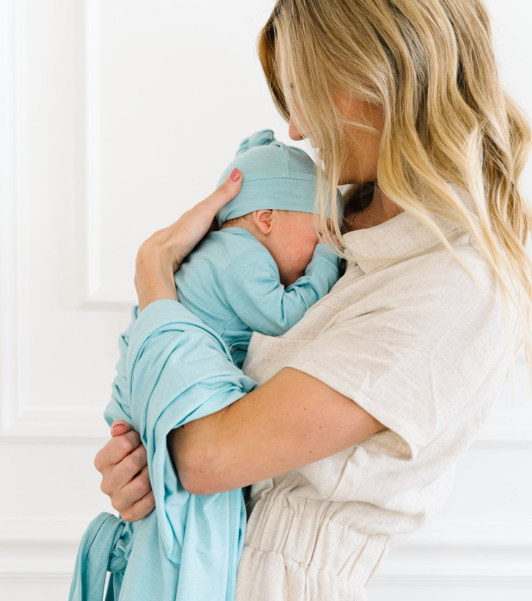 Mother holding newborn in Over Company nodo hat & gown