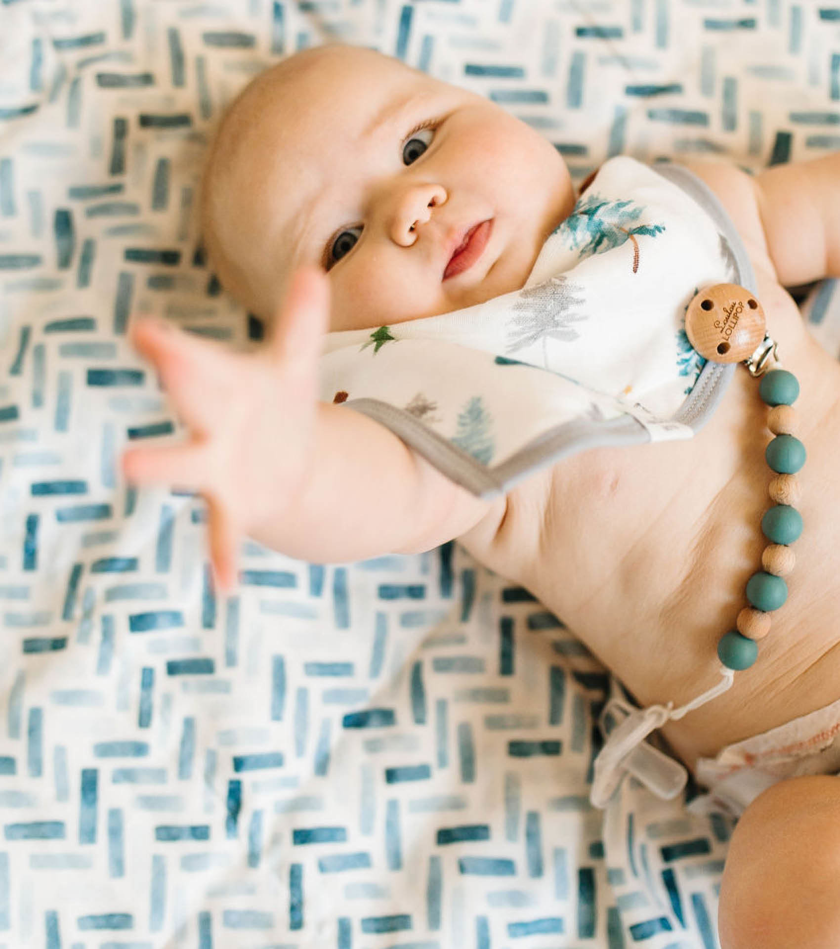 Baby reaching to the sky in wearing drool bib with pacifier clip