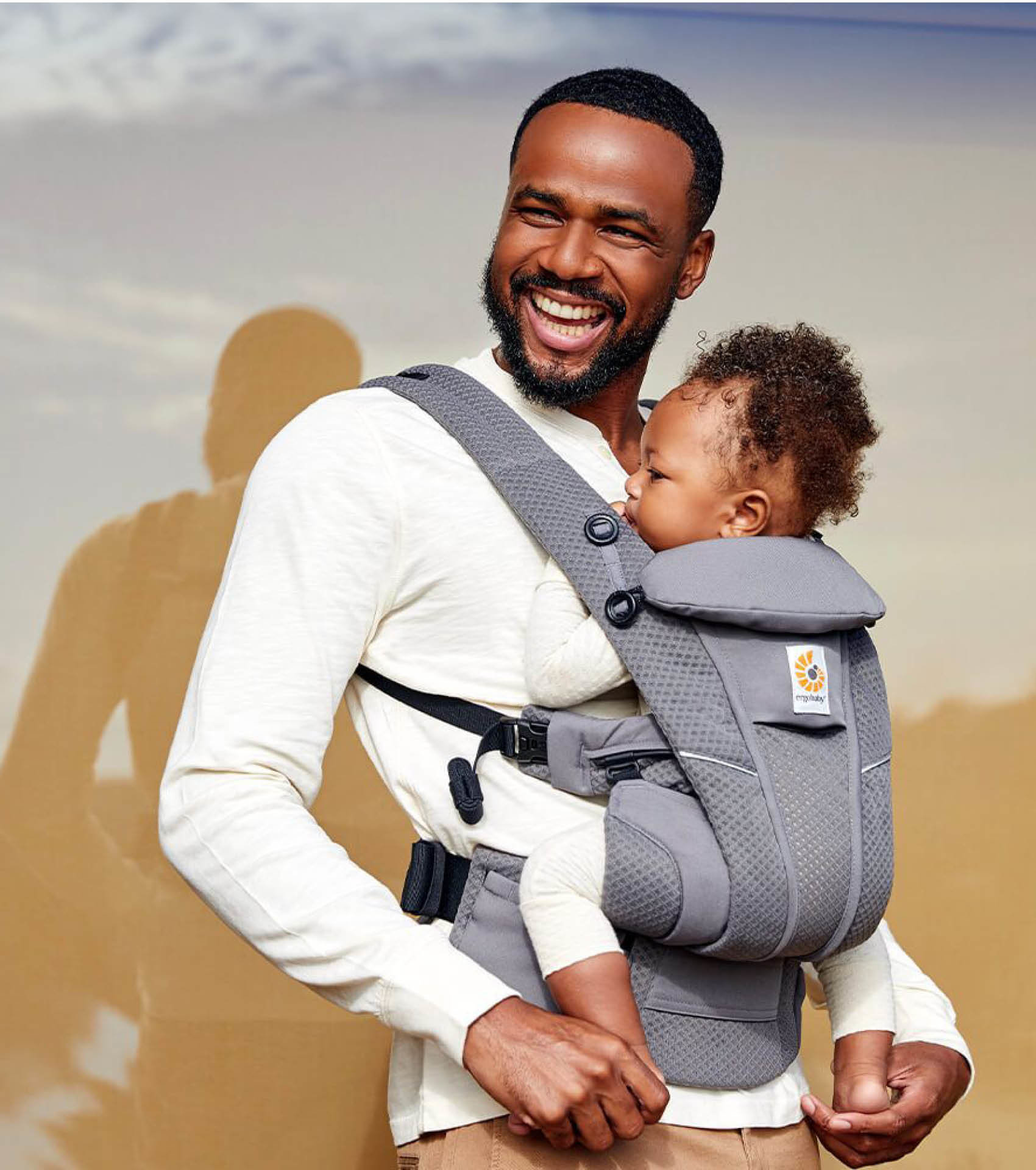Father holding baby in an ERGObaby baby structured mesh carrier