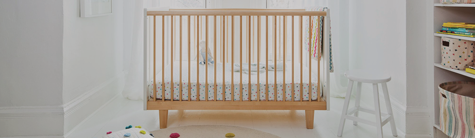 Crib in a nursery fill with Pehr cribs, storage bins, pints and pillows