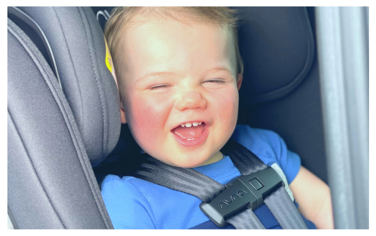 Smiling baby in Nuna RAVA car seat showing harness
